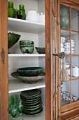 Vitrinenschrank mit offener Tür und Blick auf Geschirr aus grüner Keramik