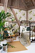 Black, retro, metal grille bed and bamboo chair in rustic, half-timbered interior with foliage plants and leaf-patterned wallpaper