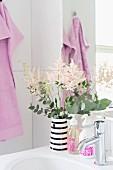 Waschbecken mit Blumendeko und pink beschrifteten Seifenspendern