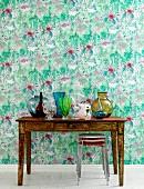 Holztisch in Vintage Stil mit bunter Glasvasen, vor Wand mit malerischem Blumenmuster auf Tapete