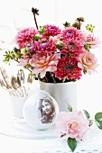 Nostalgic arrangement with vase of dahlias & snow globe on table