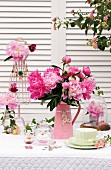 Romantic, pretty arrangement of peonies & wire necklace rack shaped like tailors' dummy on table