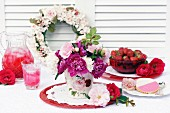 Drinks, berries & biscuits on table decorated with wreath of roses & vase of peonies