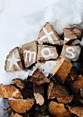 Christmas greeting painted on stacked firewood with white acrylic paint surrounded by snow