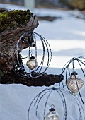 Baubles made from metal rings with silver Christmas baubles hanging from tree trunk in snowy landscape