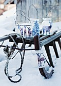 Hand-crafted lanterns made from yoghurt jars decorated with deer motifs on sledge surrounded by snow