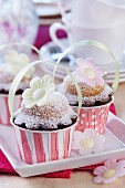 Spring muffins decorated with rice paper flowers in paper cases with handles