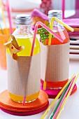 Limonadenflaschen dekorativ umwickelt mit Packpapier auf Filzuntersetzern