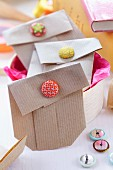Small gift bags folded from brown paper and held closed with button clips