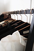 Clothes on coat hangers on metal rail