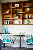 White basket chairs with turquoise cushions at worksurface below shelving with wooden back wall