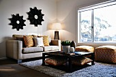 Square coffee table in front of sofa with patterned scatter cushions and matching ottomans in corner below window; mirrors with flower-shaped frames on opposite wall