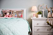 Girl's bedroom - rag doll on embroidered pillow on bed with headboard next to table lamp and soft toys on white chest of drawers