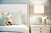 Various scatter cushions on bed with tall, white upholstered headboard next to table lamp with white ceramic base and fabric lampshade on bedside cabinet