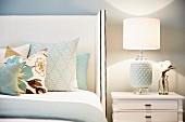 Verschiedene Kissen auf Bett mit weissbezogenem, hohem Kopfteil, neben Nachtkästchen darauf Tischleuchte mit weißem Keramikfuss und Stoffschirm