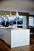 White kitchen island with integrated sink below group of pendant lamps with glossy, bottle-shaped lampshades in modern interior with floor-to-ceiling terrace doors