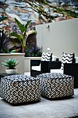 Patterned pouffes and black armchairs with patterned scatter cushions on terrace with tropical plants in raised beds against rock face and masonry wall