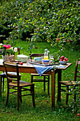 Tray of crockery on wooden plate below apple tree