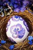 Easter egg decorated with purple, napkin decoupage violas