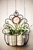 Two hand-crafted vases of snowdrops in metal basket hung on wall