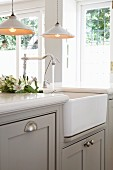 Pendant lamps with white metal lampshades above counter with integrated Belfast sink in pale kitchen
