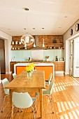 Modern shell chairs around solid wooden table in front of counter with orange drawer units in open-plan kitchen