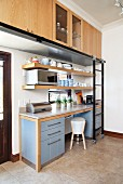 Kitchen counter with blue base units, stone worksurface and high wall units with rail and sliding ladder