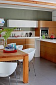 White shell chairs at solid wooden table in kitchen; drawers in wooden-fronted base units below white worksurface