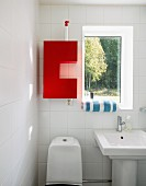 Red, wall-mounted cabinet next to window in white bathroom