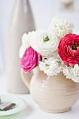 Cream narcissus and ranunculus in pale stoneware jug