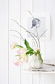 Parrot tulips in white retro vase below drawing on white wooden wall