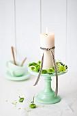 Etagere aus Jadeglas mit Kerze und kleinen Chrysanthemenblüten