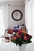 China vase of flowers on table; antique clock above writing desk in background