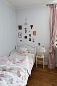 Kinderbett mit weißem Holzrahmen, daneben Nachttisch und rot-weiss gestreifter Vorhang