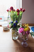 Bouquets in various glass vases on table