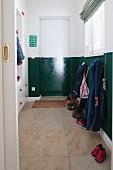 Blick durch offene Schiebetür auf Flur mit Garderobe, dunkelgrüner Streifen an Wand und Tür