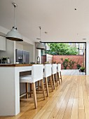 Bar stools with white loose covers at kitchen counter in open-plan designer kitchen; open folding terrace doors in background