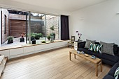Living room with sofa, wooden floor, glass wall with integrated window seat and view of courtyard