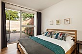 Double bed with wooden frame in simple bedroom with open terrace door in glass wall