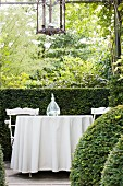 Table with long, white tablecloth and garden chairs in front of half-height hedge
