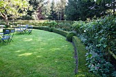Lawn edged by curved hedge with garden tables and chairs in background