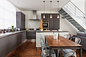 Open-plan interior in shades of grey with dining area and metal staircase