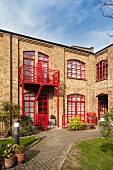 Former factory converted into residential building; red-painted window frames and balcony rails, courtyard with edged flowerbeds and paved paths