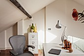 Home office on gallery - grey office chair, desk, table lamp and filing cabinet