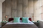 Master bedroom - pale turquoise scatter cushions on French bed against wall with concrete-look vertical tiles