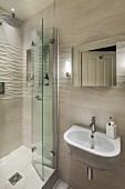 Washbasin and mirror on tiled wall with 3D structure and shower area to one side