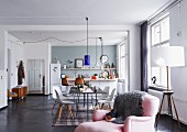 Open-plan interior with kitchen, dining area with classic chairs and pink armchair in foreground