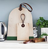 Designer chopping boards with leather straps and potted herbs on kitchen worksurface