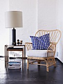 Cane armchair with cushions on table lamp on side talbe