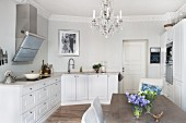 White fitted kitchen with chandelier and modern dining area in period apartment with stucco frieze